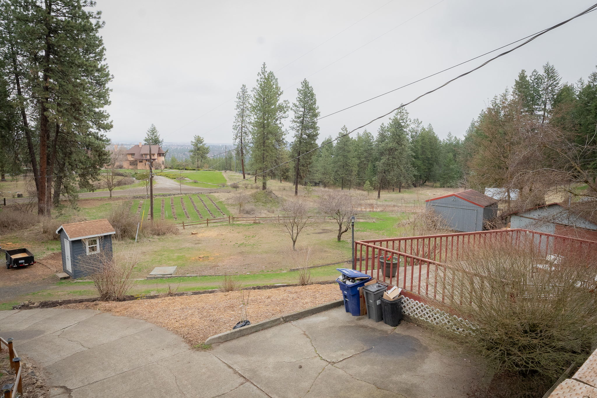 Views facing east of second large deck, well house, detached garage, seed building.