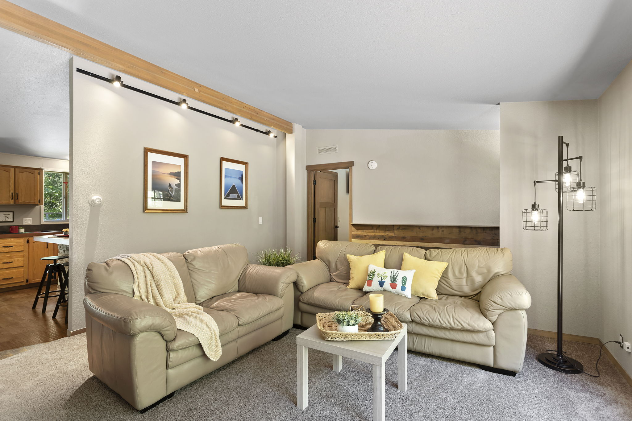 Living room has lots of space and beautiful shiplap wall at second entry to the home