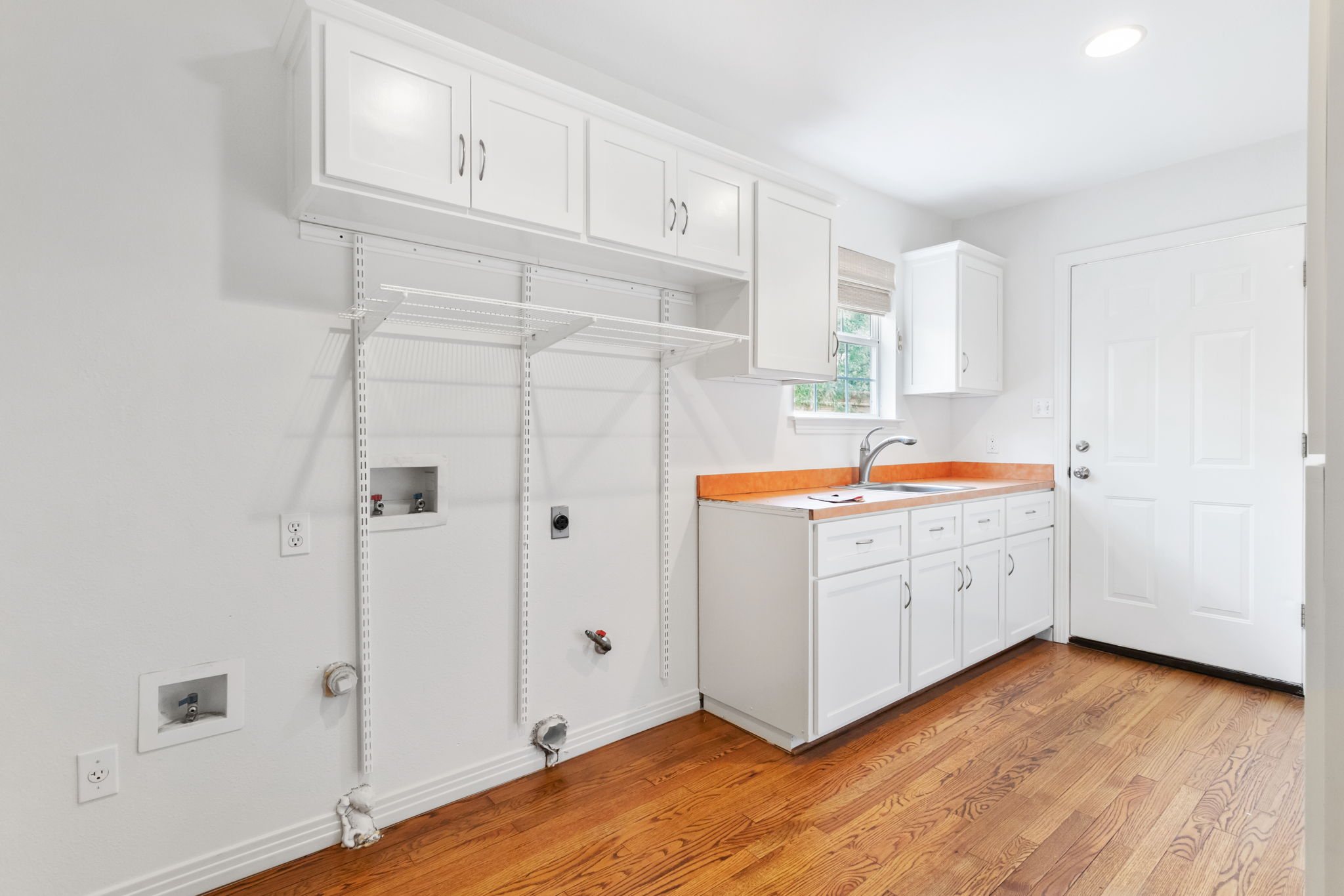 Exceptional indoor laundry room with built-in cabinets, sink, pantry and storage bench with hooks.
