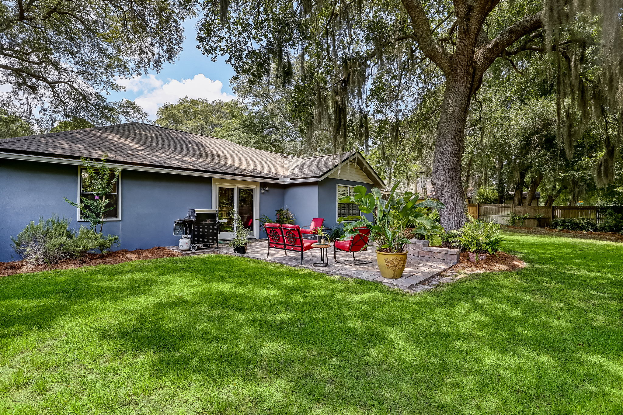 Pavered open patio shaded by majestic live oak