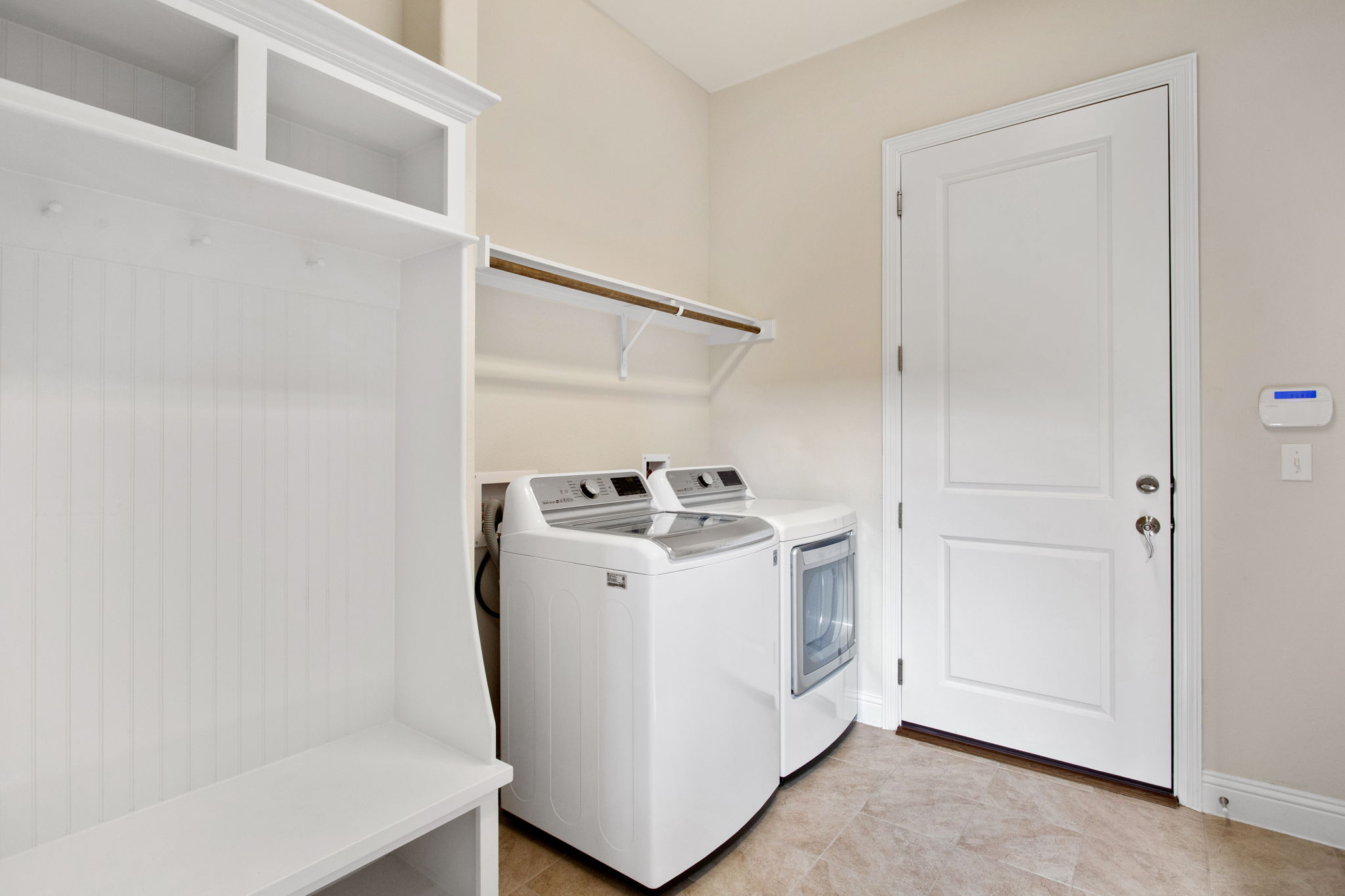 Laundry Room. The door leads to the oversized garage featuring large storage area and utility sink